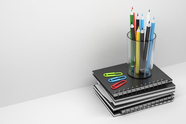 Vidro com lápis em um quadril de cadernos e revistas