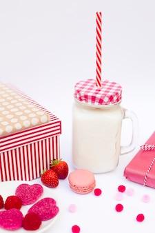Vidro com líquido e tubo perto de biscoito, doces, frutas e presentes