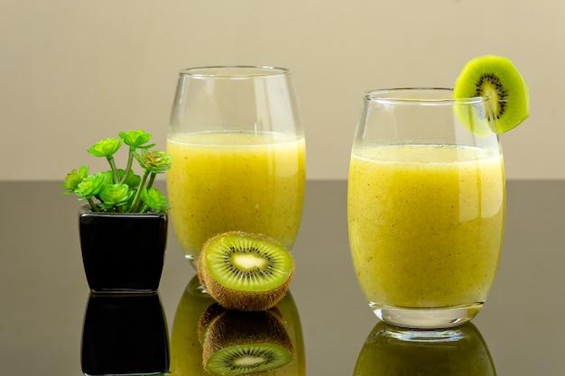 Vidro com suco de kiwi com dois meios de kiwi ao lado do vidro sob uma superfície refletiva