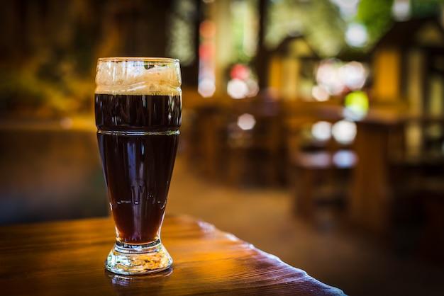 Vidro com tipos escuros de cerveja artesanal em uma barra de madeira