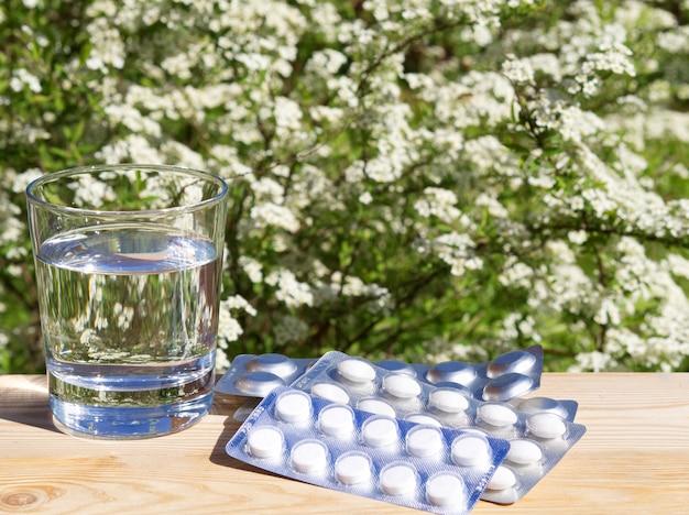 Vidro da água e dos comprimidos na tabela no fundo verde da natureza.