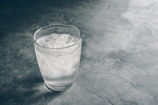 Vidro da água mineral fresca com os cubos de gelo na tabela do cimento com cor do vintage. esvazie pronto para sua exposição ou montagem do produto.