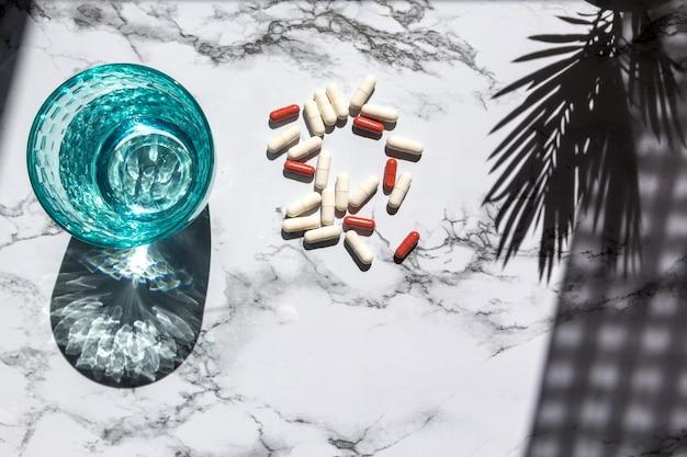 Vidro da agua potável e comprimidos no fundo de mármore com sombras da luz solar.