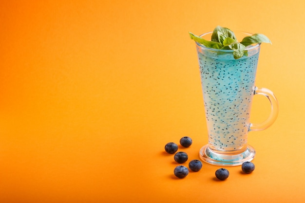Vidro da bebida colorida azul do mirtilo com sementes da manjericão. manhã, primavera, conceito de bebida saudável. vista lateral