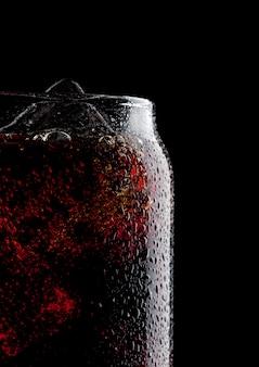 Vidro da bebida fria do refrigerante da cola com os cubos de gelo no fundo preto. macro com gotas de orvalho.