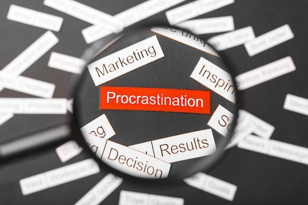 Vidro da lupa sobre a procrastinação vermelha inscrição recortada em papel. cercado por outras inscrições em um escuro. palavra nuvem .