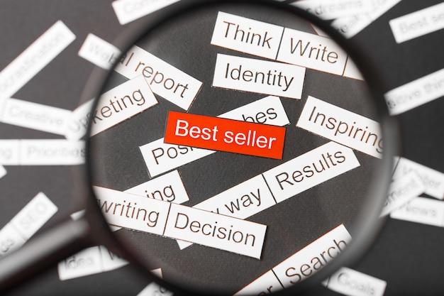 Vidro da lupa sobre o best-seller vermelho inscrição recortado em papel. cercado por outras inscrições. conceito de nuvem de palavras.
