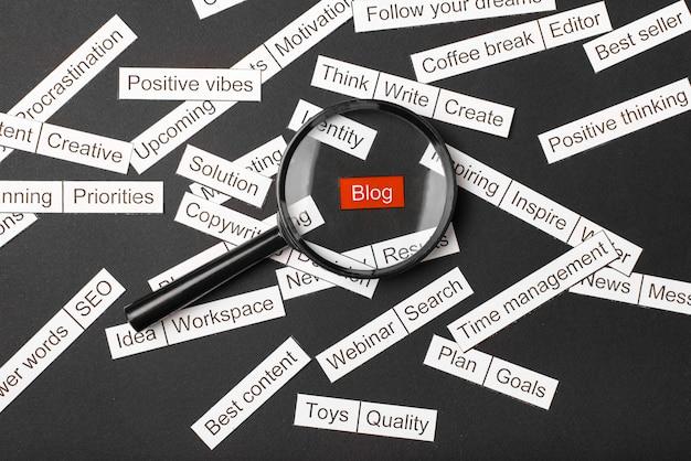Vidro da lupa sobre o blog de inscrição vermelho cortado em papel. rodeado por outras inscrições em um fundo escuro. conceito de nuvem de palavras.