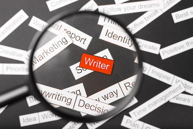 Vidro da lupa sobre o escritor de inscrição vermelho cortado em papel, rodeado por outras inscrições