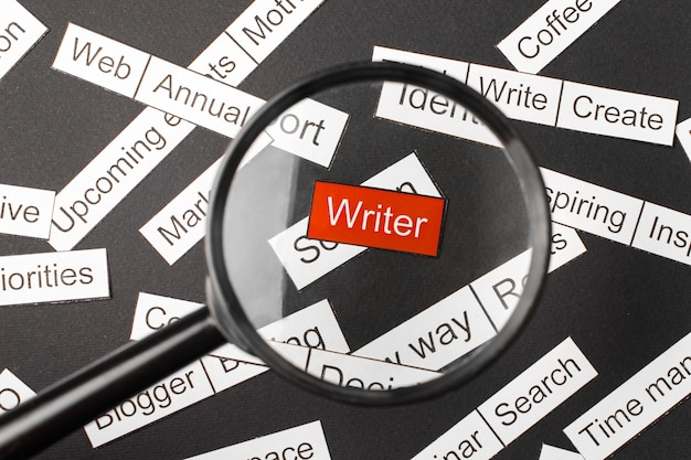 Vidro da lupa sobre o escritor de inscrição vermelho recortado em papel. rodeado por outras inscrições em um fundo escuro. conceito de nuvem de palavras.