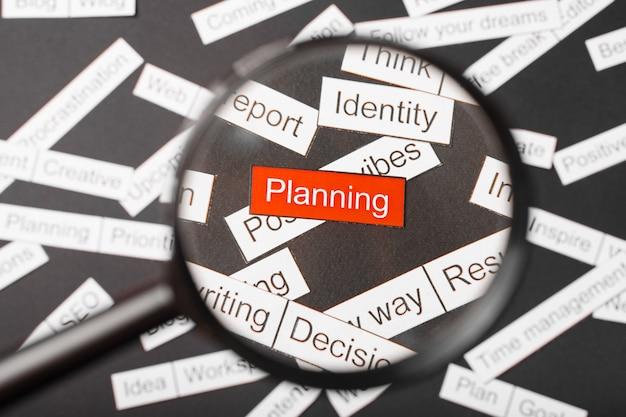Vidro da lupa sobre o planejamento de inscrição vermelho cortado em papel. rodeado por outras inscrições em um fundo escuro. conceito de nuvem de palavras.