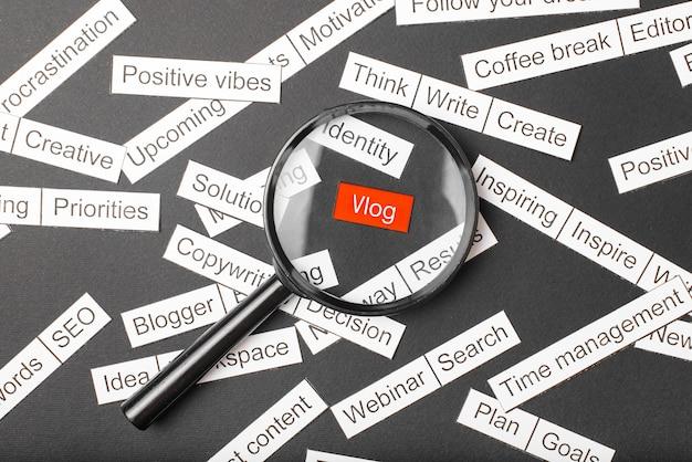 Vidro da lupa sobre o vlog de inscrição vermelho cortado em papel. cercado por outras inscrições em um espaço escuro. conceito de nuvem de palavras.
