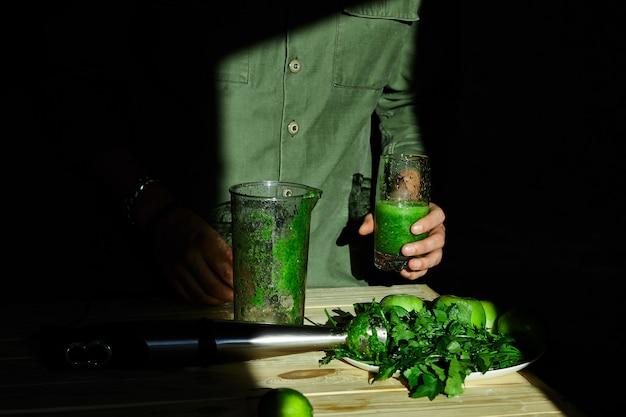 Vidro da posse da mão do homem com o batido saudável da desintoxicação, cozinhando com o misturador com espinafres dos frutos frescos e dos verdes, conceito da desintoxicação do estilo de vida. conceito de desintoxicação de estilo de vida. bebidas veganas.