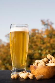 Vidro de baixo ângulo com cerveja ao lado de amendoins