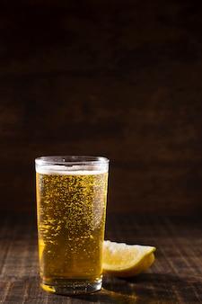 Vidro de cópia-espaço com espuma de cerveja na mesa