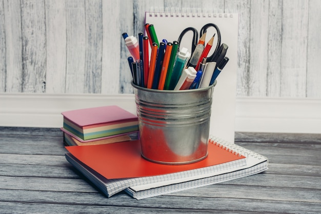 Vidro de ferro com marcadores de lápis e tesoura e bloco de notas na mesa de madeira com tinta aquarela