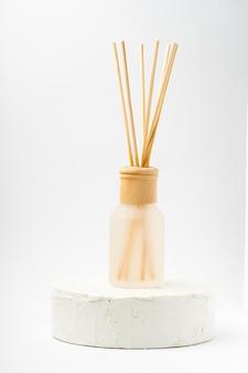 Vidro de garrafa de aroma e varas de madeira, ficar no pódio de cimento branco sobre fundo branco.