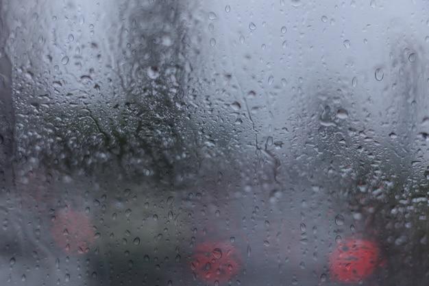 Vidro de janela de carro de água com fundo da rua na estação chuvosa