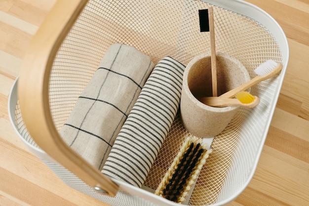Vidro de mármore com escovas de dente e toalha enrolada em balde de plástico