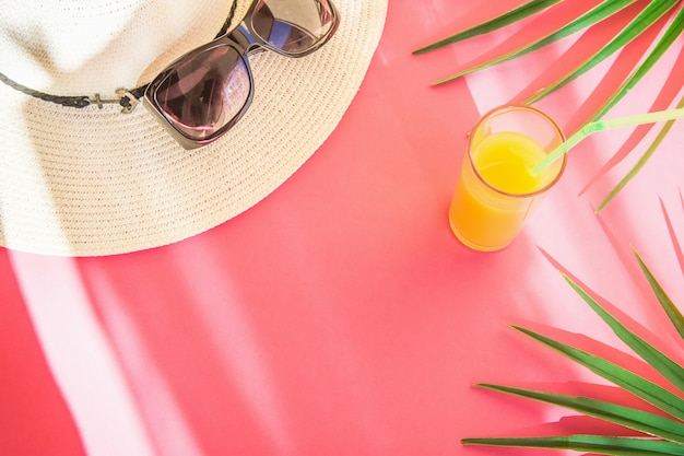Vidro de óculos de sol de chapéu de palha com folhas de palmeira de suco de frutas tropicais frescas