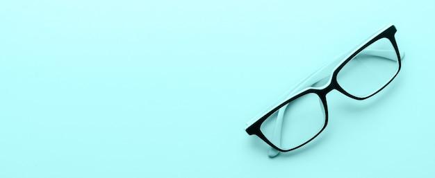 Vidro de olho de óculos modernos isolado na superfície azul. vista do topo. banner com espaço de cópia.