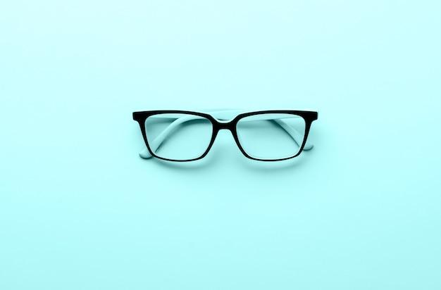 Vidro de olho de óculos modernos isolado na superfície azul.
