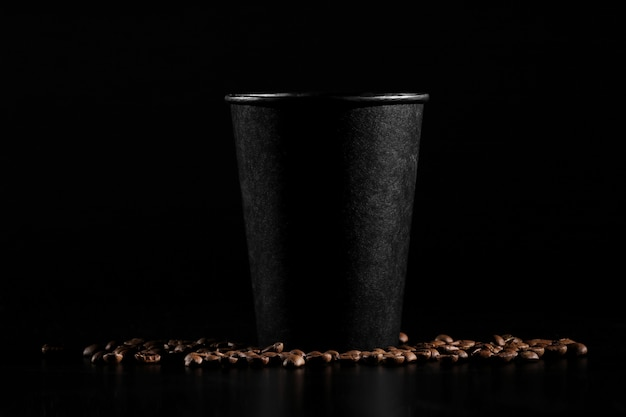 Vidro de papel preto no fundo preto. grãos de café sobre um fundo escuro.