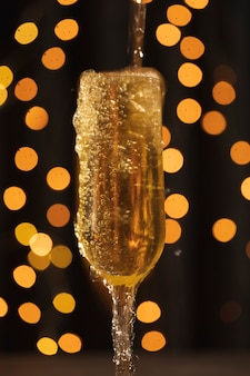 Vidro de vista frontal com champanhe com espuma