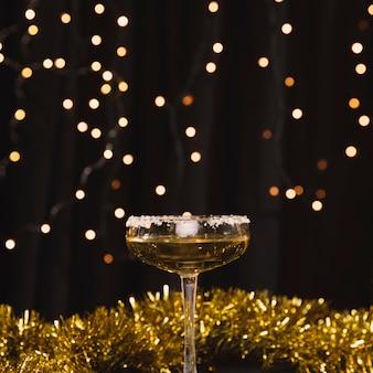 Vidro de vista frontal com champanhe e decorações douradas