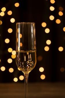 Vidro de vista frontal com champanhe na festa de ano novo