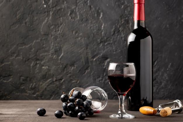 Vidro de vista frontal com vinho tinto ao lado da garrafa de vinho