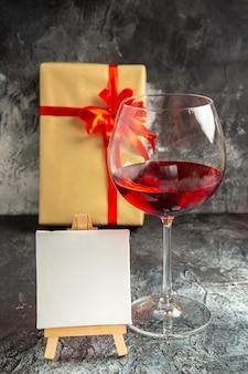 Vidro de vista frontal de tela branca de vinho presente de natal em cavalete de madeira no escuro