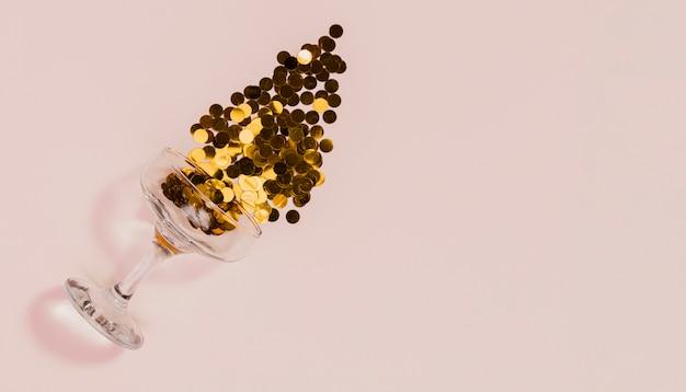 Vidro derramando confete dourado sobre fundo rosa