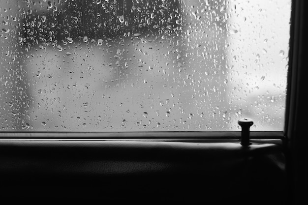 Vidro do carro com gotas de chuva com espaço de cópia. atmosférico fundo monocromático com pingos de chuva.
