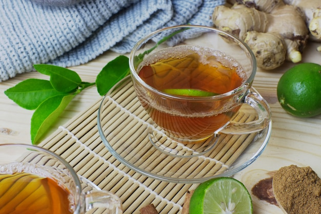 Vidro do chá do limão e do gengibre com ofício na tabela de madeira.