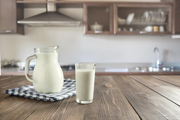 Vidro do leite e do jarro frescos na mesa de madeira com cozinha do borrão como o fundo.
