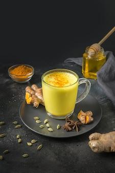 Vidro do leite indiano indiano do latte da cúrcuma com raiz da curcuma, pó no preto. tiro vertical.