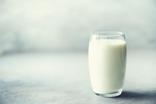 Vidro do leite no espaço concreto cinzento da cópia do woth do fundo.