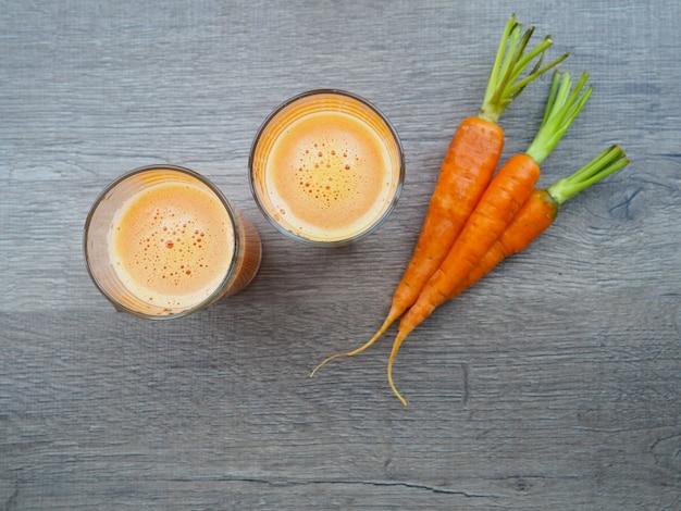 Vidro do suco de cenoura fresco com os vegetais no fundo de madeira. tiro alto
