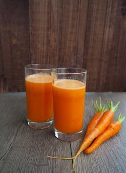 Vidro do suco de cenoura fresco com os vegetais no fundo de madeira.