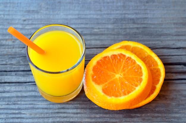 Vidro do suco de laranja e fatias frescos de fruta alaranjada na tabela de madeira rústica.