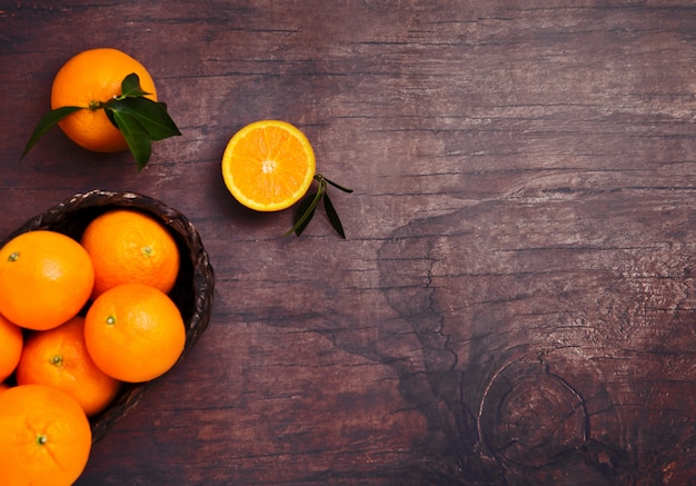 Vidro do suco orgânico fresco do batido de laranja com as laranjas cruas no fundo escuro de madeira. vista superior.