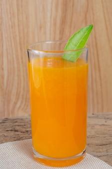 Vidro do sumo de laranja colocado na madeira.