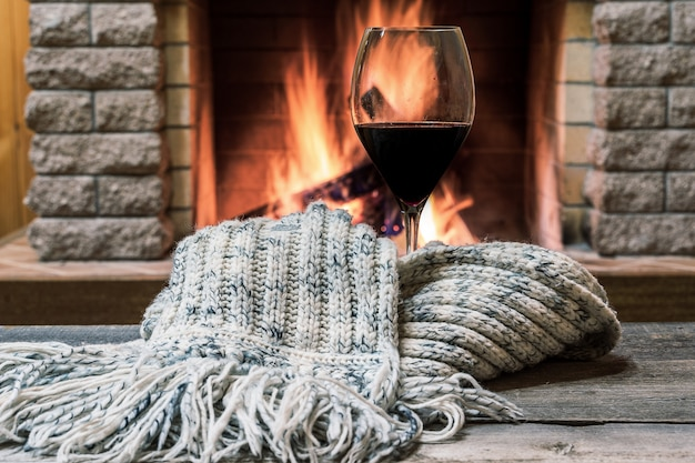 Vidro do vinho contra o fundo acolhedor da chaminé, conceito de hygge.