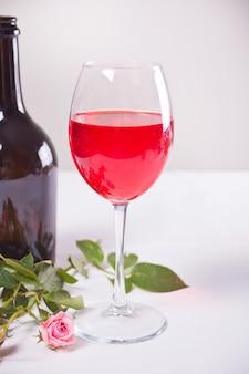 Vidro do vinho de uva vermelha com garrafa e rosas no fundo. conceito de jantar romântico.