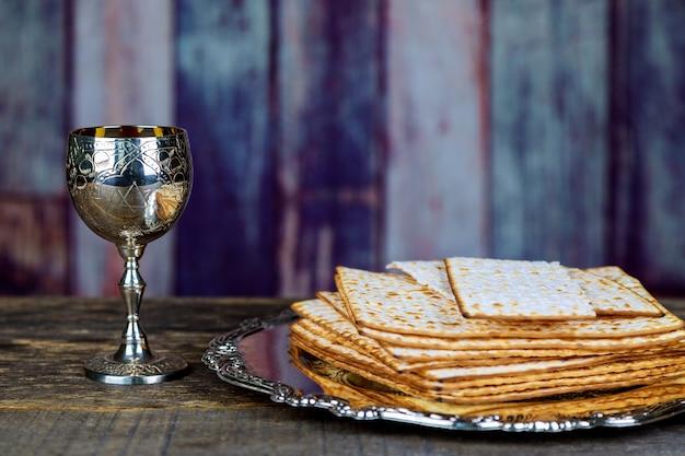 Vidro do vinho do passover e do close up do matzah. textura borrada retroiluminada do matzah no fundo.