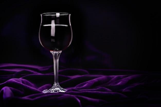 Vidro do vinho vermelho na tela rippled roxa de veludo.