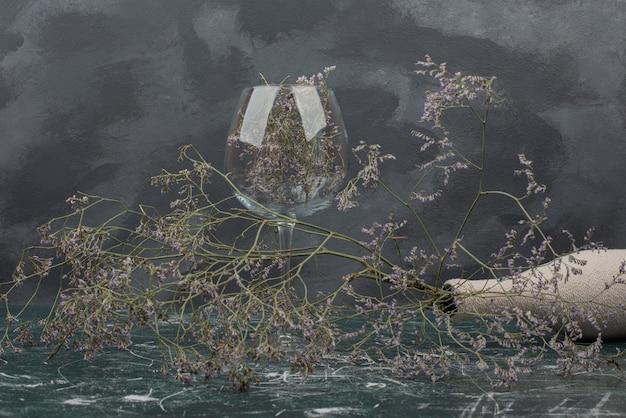 Vidro e garrafa com flores murchas na mesa de mármore.