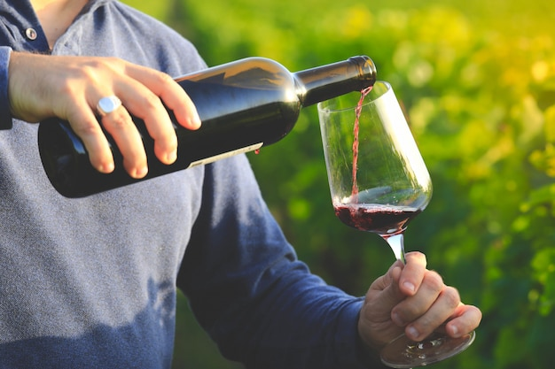 Vidro e garrafa de vinho tinto em foco seletivo no copo de vinho. derramando vinho tinto ao pôr do sol