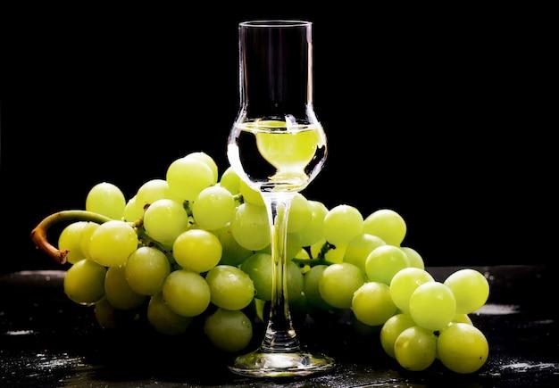 Vidro grappa com cacho de uvas brancas